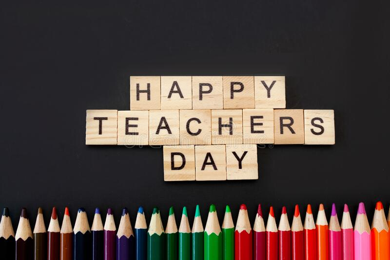 Happy teachers day card. Wooden letters spelling happy teachers day on black background with coloured pencils frame royalty free stock image