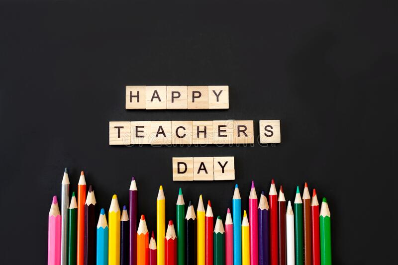 Happy teachers day card. Wooden letters spelling happy teachers day on black background with coloured pencils frame royalty free stock photography