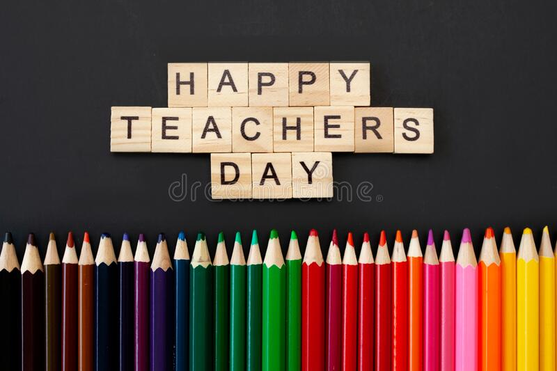 Happy teachers day card. Wooden letters spelling happy teachers day on black background with coloured pencils frame royalty free stock photos
