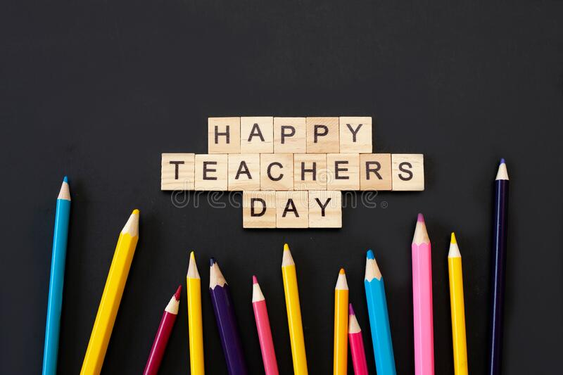 Happy teachers day card. Wooden letters spelling happy teachers day on black background with coloured pencils frame royalty free stock images