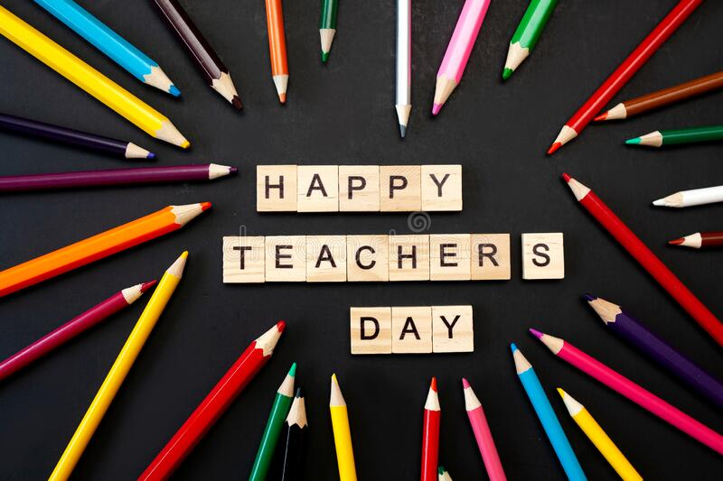 Happy teachers day card. Wooden letters spelling happy teachers day on black background with coloured pencils frame stock photo