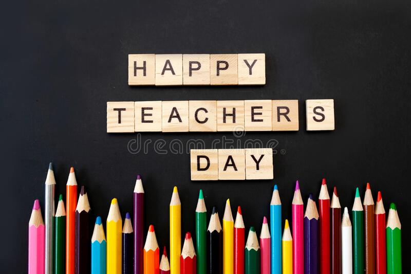 Happy teachers day card. Wooden letters spelling happy teachers day on black background with coloured pencils frame stock image