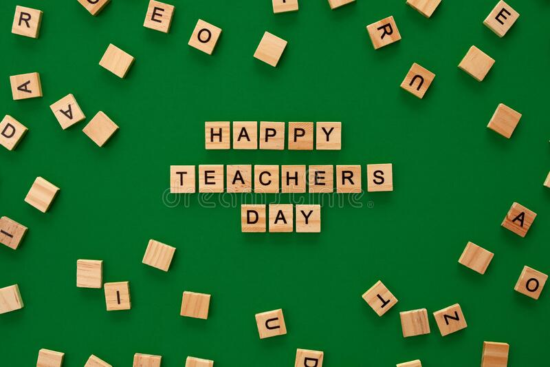 Happy teachers day card. Wooden letters spelling Happy teachers day on green dark backgrund royalty free stock photo
