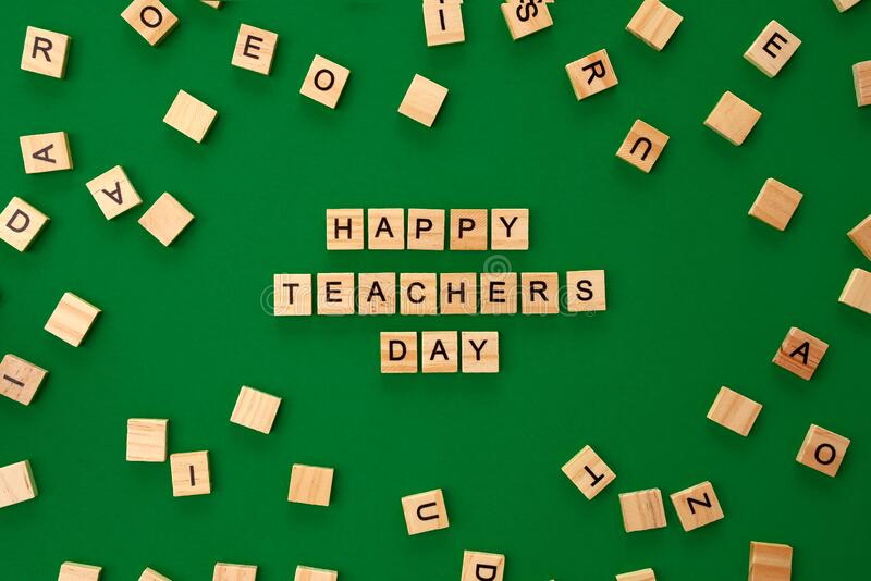 Happy teachers day card. Wooden letters spelling Happy teachers day on green dark backgrund royalty free stock photography