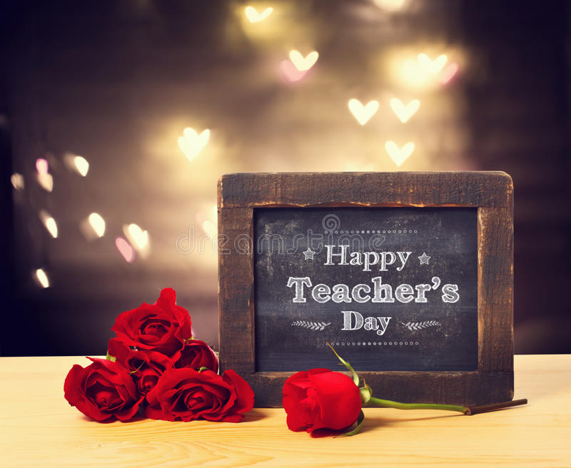 Happy Teachers day message with roses. Happy Teachers day message on a small chalkboard with red rosesn royalty free stock photo