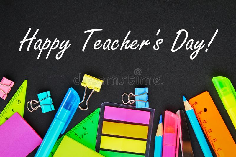 Happy Teachers Day. School supplies on blackboard background ready for your design. Flat lay. Top view. Happy Teachers Day. School supplies on blackboard stock photo