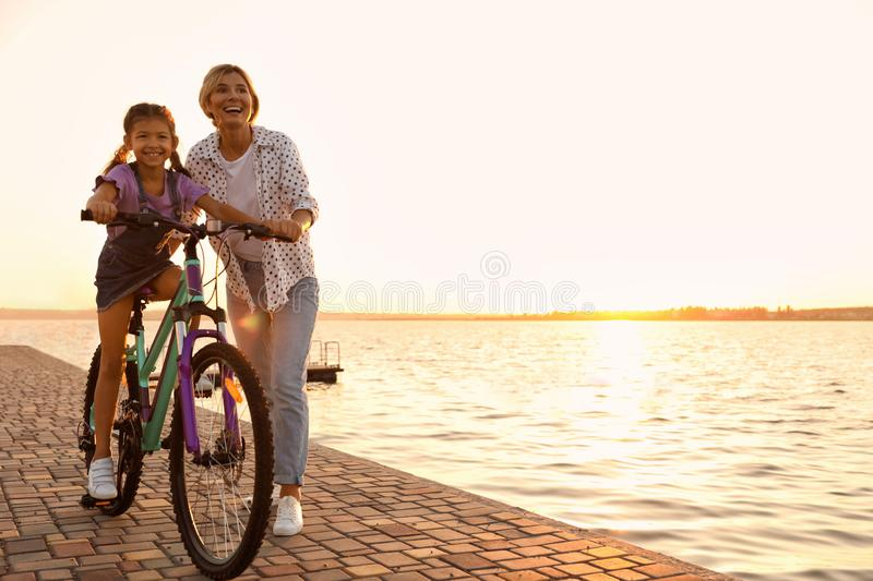 Happy  teaching her daughter to ride bicycle near river at sunset. Happy mother teaching her daughter to ride bicycle near river at sunset stock photo