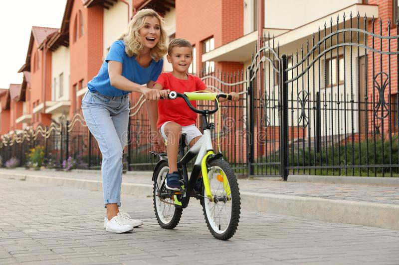 Happy  teaching her son to ride bicycle in city. Happy mother teaching her son to ride bicycle in city stock photography