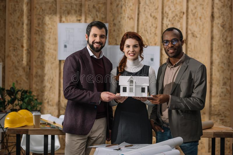 happy team of architects holding miniature model of building royalty free stock photography
