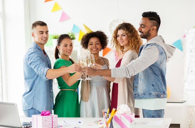 Happy team with champagne at office birthday party. Corporate, celebration and holidays concept - happy team clinking glasses of non-alcoholic sparkling wine at stock images