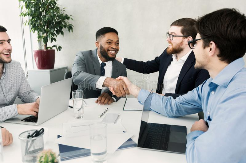 Happy team congratulating successful worker by shaking hands stock images