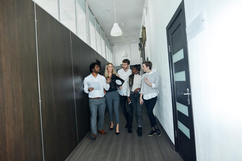 Happy team of corporate professionals walking and talking indoors royalty free stock images
