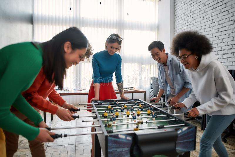 Happy team. Group of young and excited multicultural people in casual wear playing table soccer in the modern office and royalty free stock images