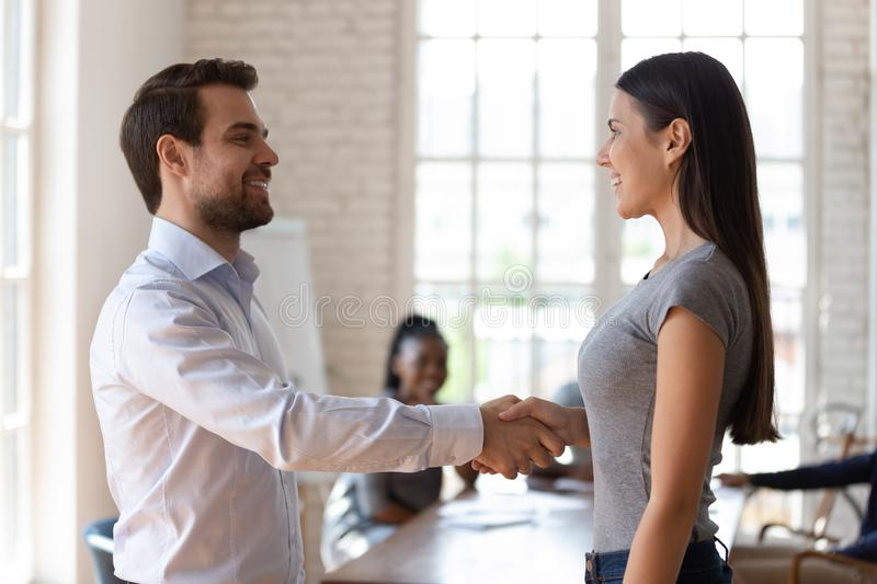 Happy team leader shaking hands with smiling female employee. stock images