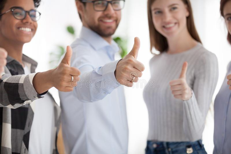 Happy team of multiracial business people with thumbs up stock photo