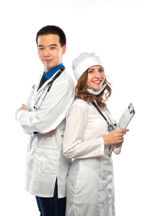 Happy team of two physicians standing back to back with arms fol stock image