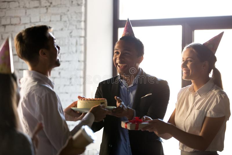 Happy teammates congratulating happy birthday to colleague. Happy workmates diverse business people congratulate happy birthday colleague giving cake with royalty free stock image