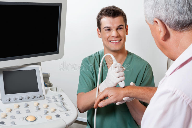Happy Technician Scanning Male Patient's Hand stock photography