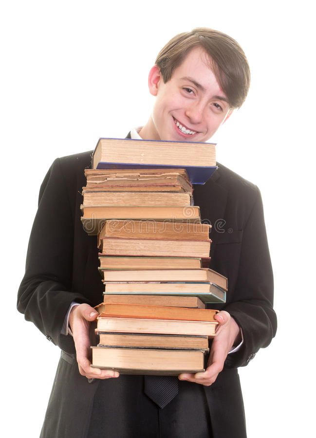 Happy teen boy with arm load of books royalty free stock image