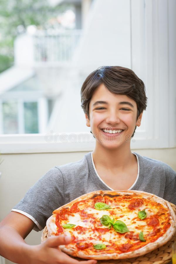 Happy teen boy cooked pizza. Cheerful smiling teenager holding homemade pizza, enjoying traditional tasty italian food royalty free stock image
