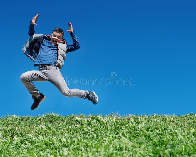 Happy teen boy jumping on meadow stock photo