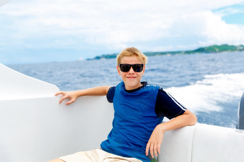 Happy teen boy in sunglasses on the yacht. Tropical sea in the b royalty free stock images
