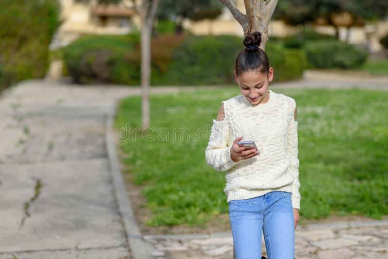Happy teen child works in the phone, looking into it,pay goods.Teen girl young blogger reading good news on mobile phone royalty free stock photography