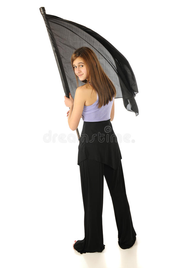 Happy Teen Color Guard. A back fiew of an attractive teen color guard looking over her shoulder as she twirls her flag. Isolated on white. Motion blur on flag stock images