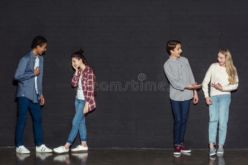 Happy teen couples talking. On black stock image