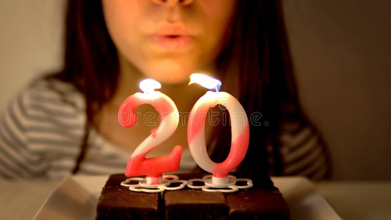 Happy teen girl celebrating her 20th birthday and blowing candles royalty free stock images