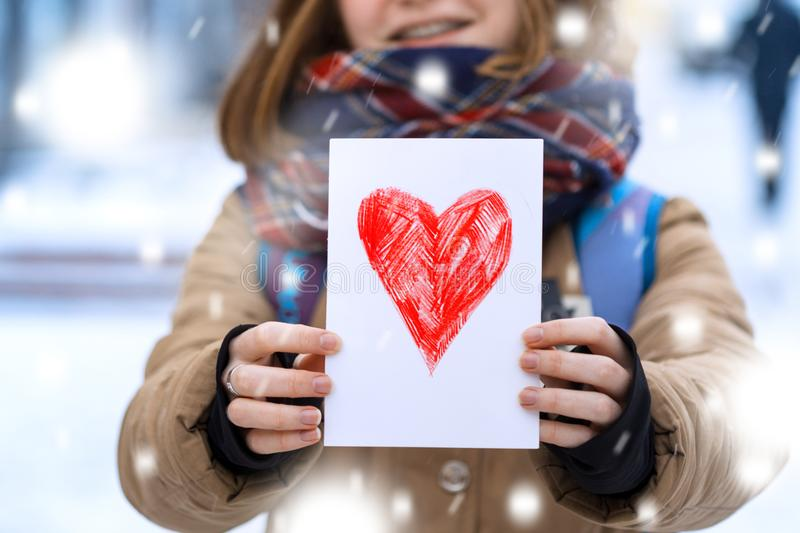 Girl with heart. Happy teen girl holding drawing with a heart on the valentines day stock photo