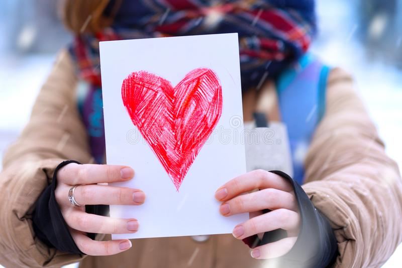 Girl with heart. Happy teen girl holding drawing with a heart on the valentines day royalty free stock photo