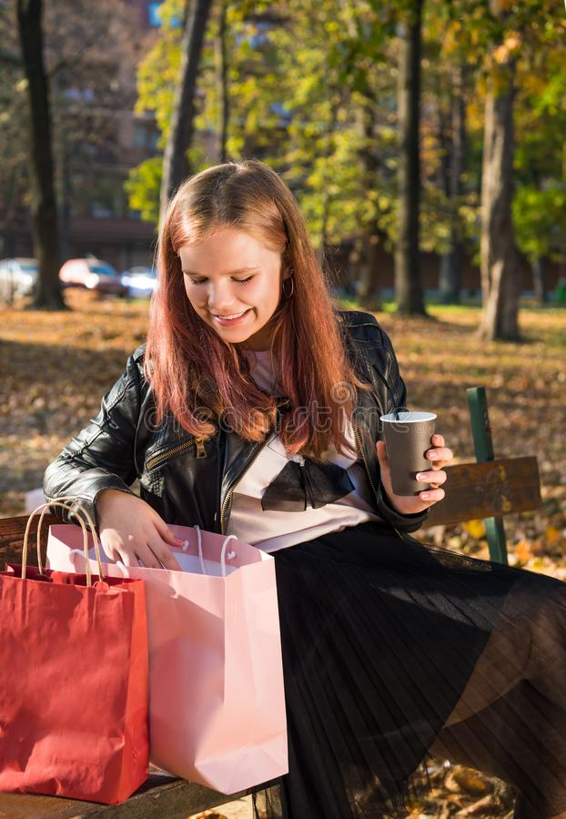 Happy teen girl holding takeaway coffee cups in sunny autumn park royalty free stock image
