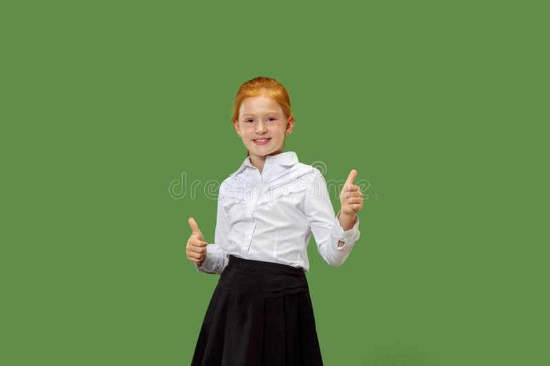 The happy teen girl standing and smiling against p green background. stock photos