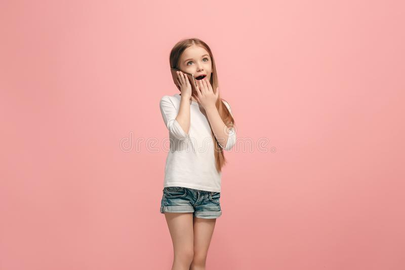 The happy teen girl standing and smiling against pink background. stock images