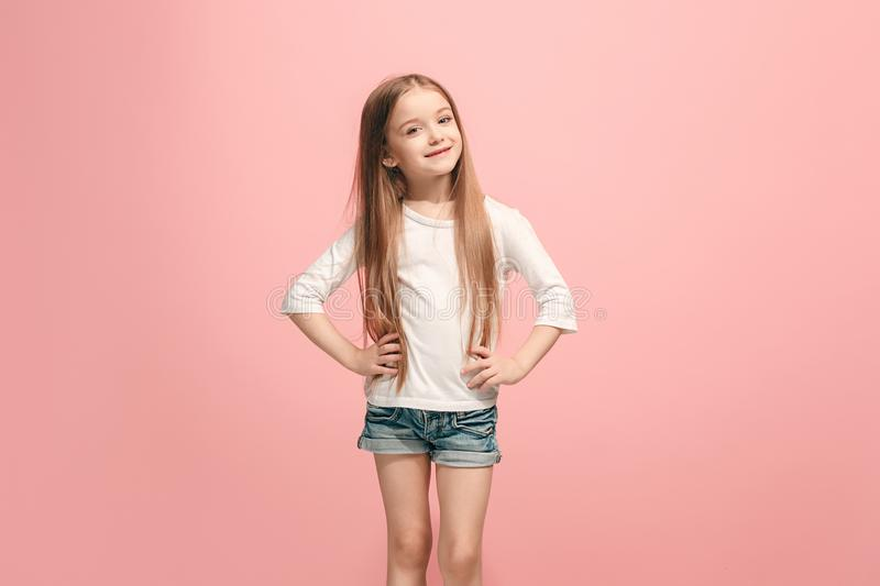 The happy teen girl standing and smiling against pink background. royalty free stock photo