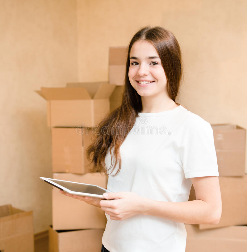 Happy teen girl with tablet computer standing on a background of boxes stock images
