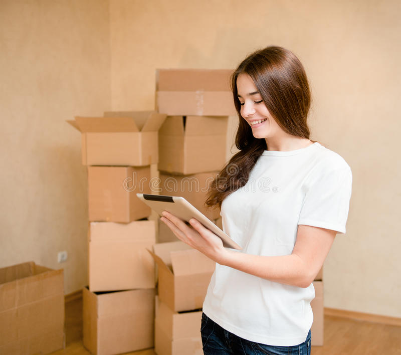 Happy teen girl with tablet computer standing on a background of boxes stock photo