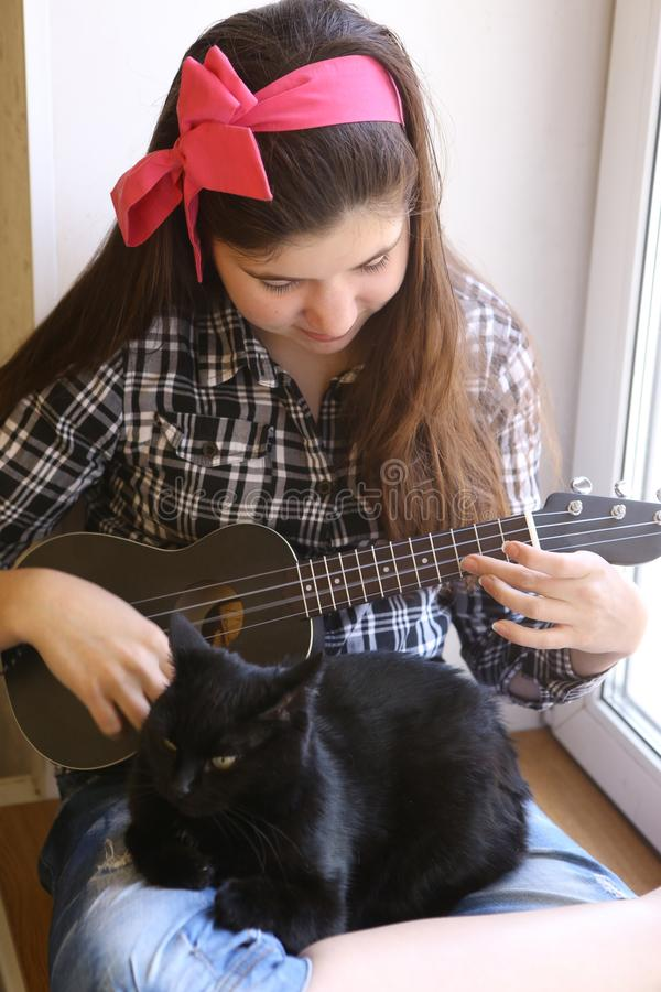 Happy teen girl with ukulele guitar in checked shirt and jeans playing royalty free stock photos