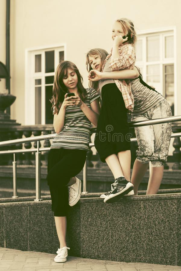 Happy teen girls calling on mobile phones against a school building. Group of happy teen girls calling on mobile phones against a school building royalty free stock images
