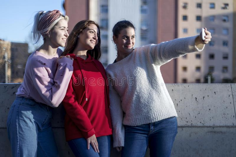 Happy teen girls taking selfie in park with mobile phone outdoors stock photo