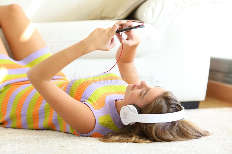 Happy teen listening to music wearing colorful dress stock photo