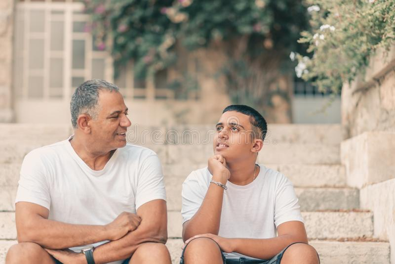Happy teen young boy rest on stairs speak with elderly father enjoy leisure family weekend. stock photography