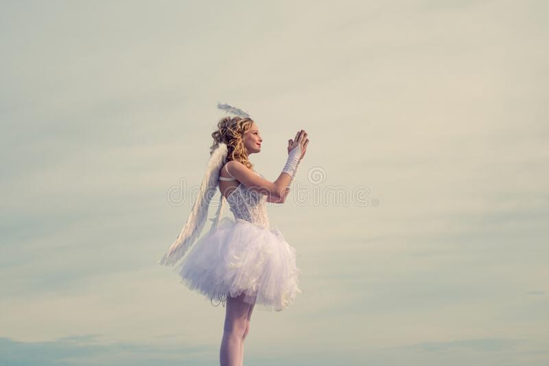 Happy teenage angel girl pray. Child with angelic character. Girl dressed as an angel on a light heaven background royalty free stock images