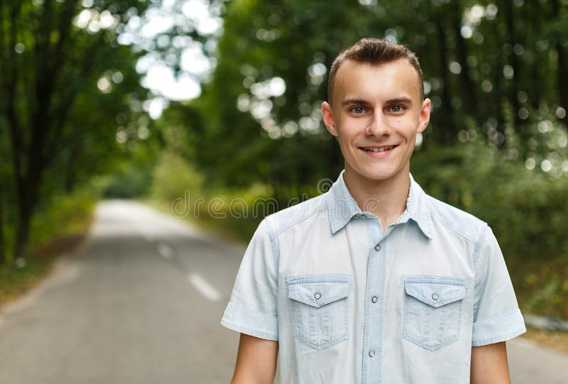 Happy teenage boy. Happy young man in the park forest royalty free stock photography