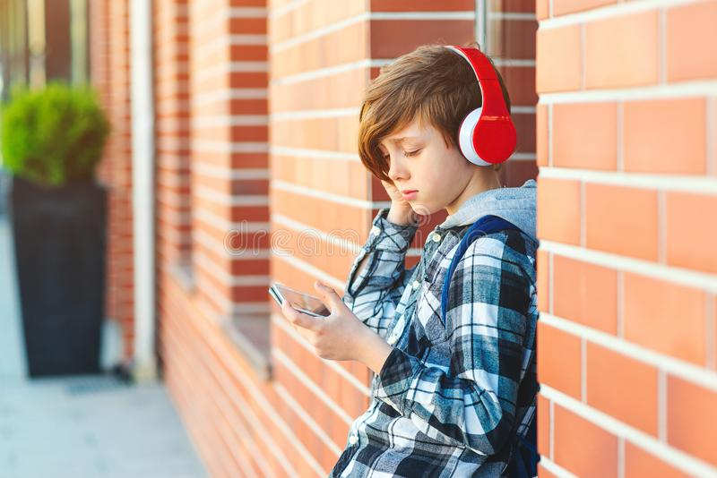Happy teenage boy with headphones outdoors. Boy listening to music. Teen using phone after school. Fashion, lifestyle, technology.  royalty free stock images