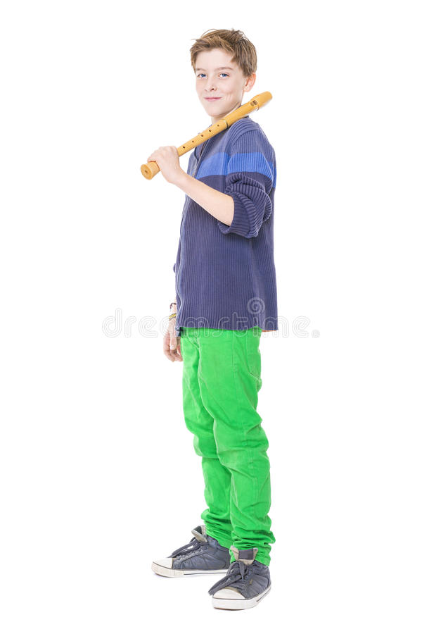 Happy teenage boy holding a flute on his shoulder royalty free stock photo
