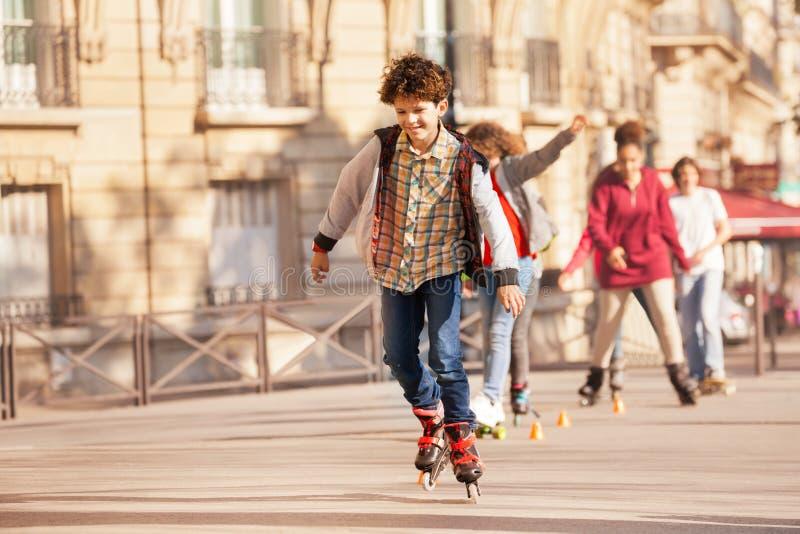 Happy teenage boy roller skating at city side walk royalty free stock image