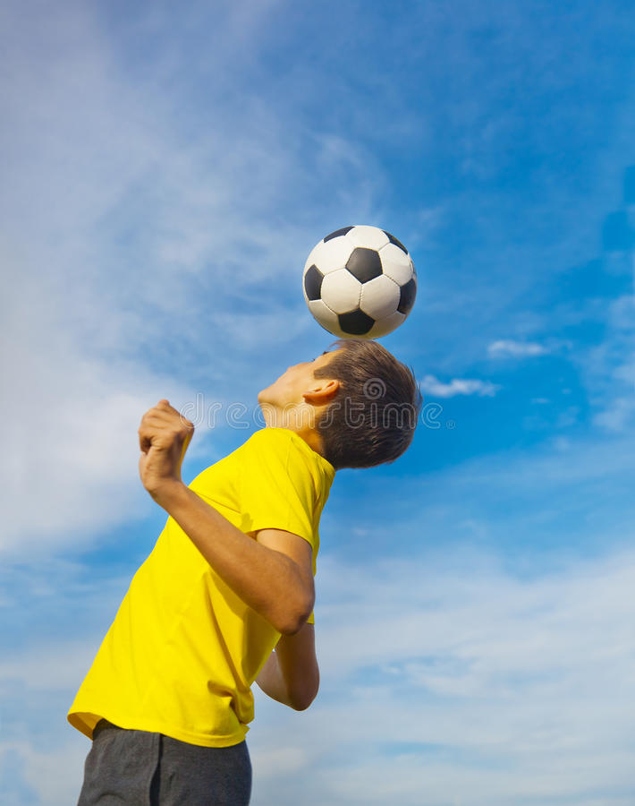 happy teenage boy with a soccer ball on his head on blue sky background stock photography