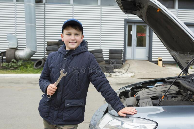 Happy teenage boy with wrench at car service, helps father. Repair service royalty free stock photo
